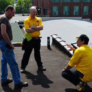 Two commercial roofing contractors talking with the building owner about his roof.