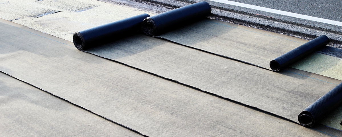 Rolls of EPDM roofing laid out on a commercial roof.